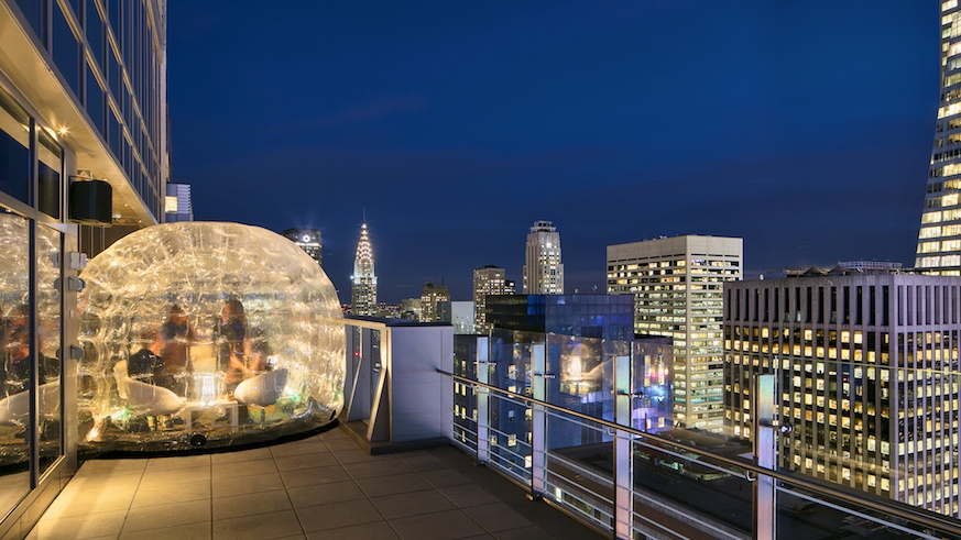 Huddle up inside a rooftop bubble for Midtown views from river to river at Bar 54.